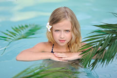 Portrait of little girl. In tropical style in a swimming pool Royalty Free Stock Photos