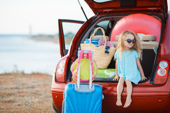 Portrait of a little girl in the trunk of a car. A little girl,a brunette with long curly hair,dressed in a striped sailor shirt,dark sun glasses,and a journey Stock Photography