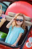 Portrait of a little girl in the trunk of a car. A little girl,a brunette with long curly hair,dressed in a striped sailor shirt,dark sun glasses,and a journey Royalty Free Stock Photo