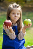 Portrait of a little girl with two large apples Stock Photos