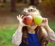 Portrait of a little girl with two large apples Royalty Free Stock Photography