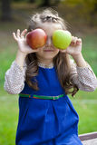 Portrait of a little girl with two large apples Stock Images