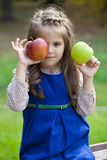Portrait of a little girl with two large apples Stock Image
