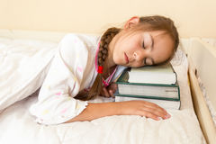 Portrait of little girl using pile of books instead of pillow Stock Photos