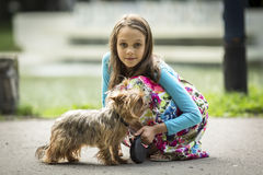 Portrait of  little girl on a walk with her little dog. Royalty Free Stock Images