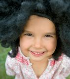 Little girl wearing a big black wig and smiling. Portrait of little girl wearing a big black wig and smiling royalty free stock images