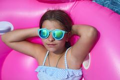 Portrait of little girl wearing sunglasses on inflatable flamingo swim float. Enjoying pool party in summer royalty free stock photo