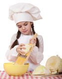 Portrait of a little girl in a white apron and chefs hat shred c Royalty Free Stock Image