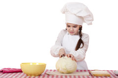 Portrait of a little girl in a white apron and chefs hat shred c. Abbage in the kitchen, isolated on white background Royalty Free Stock Photography