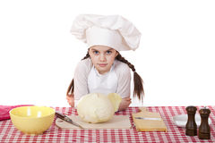 Portrait of a little girl in a white apron and chefs hat shred c. Abbage in the kitchen, isolated on white background Royalty Free Stock Photos