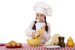 Portrait of a little girl in a white apron and chefs hat shred c. Abbage in the kitchen, isolated on white background Stock Image