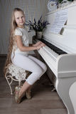 Portrait of little girl in white dress playing piano. Concept of music study and arts Stock Photography