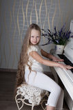 Portrait of little girl in white dress playing piano. Stock Photos