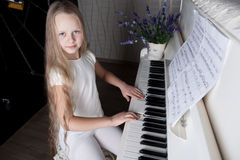 Portrait of little girl in white dress playing piano. Royalty Free Stock Image