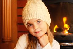 Portrait of little girl in white hat by fireplace Royalty Free Stock Images
