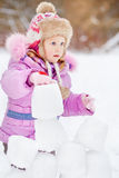 Portrait of little girl who builds wall of snow blocks Royalty Free Stock Images