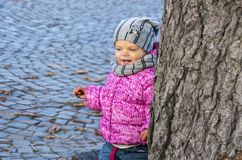 Portrait of a little girl who looks out from behind a tree Stock Photo