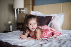 Portrait of a little girl who played on the bed in the bedroom Stock Photos