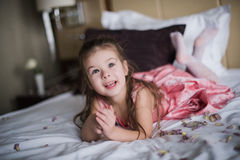 Portrait of a little girl who played on the bed in the bedroom Stock Photo