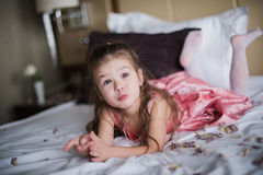 Portrait of a little girl who played on the bed in the bedroom Royalty Free Stock Image
