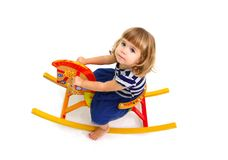 Portrait of little girl who riding on wooden horse isolated Royalty Free Stock Images