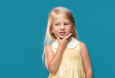 Portrait of a little girl who thinking. The little girl is thinking about something on a blue background Stock Photos