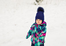 Portrait of a little girl in winter clothes in snow forest at snowflakes background.  Stock Photo