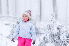 Portrait of a little girl in winter hat in snow forest at snowflakes background. Outdoors winter leisure and lifestyle with kids Royalty Free Stock Photos