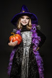 Portrait of little girl in witch costume with pumpkin. Halloween character Royalty Free Stock Image