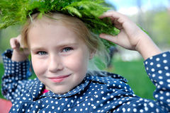 Portrait of little girl with wreath from grass. Portrait of little girl with wreath from grass sitting on the banch Royalty Free Stock Photo