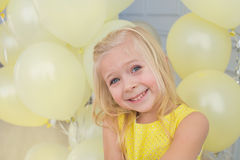 Portrait of a little girl with a yellow balloons. Portrait of a smiling little girl in a yellow dress with a yellow balloons Royalty Free Stock Photos