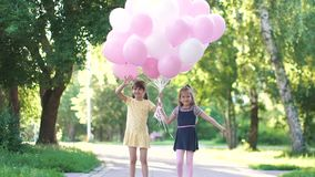 Portrait of little girls with balloons. Two little girlfriends holding hands, smiling and looking at the camera. slow. Children run through the Park with a huge stock video footage
