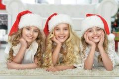 Portrait of little girls in Santa hats. Portrait of three cute little girls in Santa hats lying on the floor stock photo