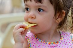 Girl eating potato chips. Portrait of a little gril in pink dress eating potato chips stock photos