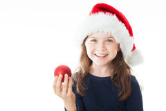 Portrait of a little happy cute Christmas girl. Portrait of a little cute girl wearing a Christmas Hat, holding a red Christmas ball, looking straight into the Royalty Free Stock Images