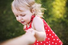 Portrait of a happy girl. the child holds the hand of the parent and plays royalty free stock image