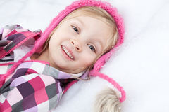 Portrait of little happy girl lying on snow Stock Photo