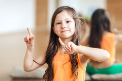Portrait of a little happy girl in sports clothes, orange top, close-up, fitness for children stock photo