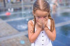 Portrait of little happy wet girl outdoors Stock Image