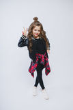 Portrait of little hipster girl in bomber jacket. Posing. Curly modern hairstyle. Showing peace by fingers. Smiling Royalty Free Stock Photos