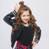 Portrait of little hipster girl in bomber jacket showing horns by hands. Posing. Curly modern hairstyle. Showing peace Royalty Free Stock Images