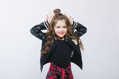 Portrait of little hipster girl in bomber jacket showing horns by hands. Posing. Curly modern hairstyle. Showing peace Stock Photo