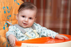 Portrait of a little kid. Half-year-old kid sitting on a chair for feeding and looking directly into the camera. His face kind smile Royalty Free Stock Images
