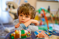 Portrait of little kid boy sad on birthday. child with lots of toy
