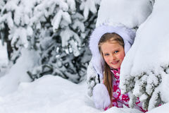 Portrait of little kid girl in winter clothes plying in deep snow. Stock Image