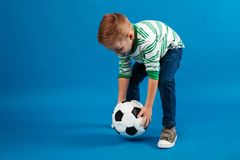 Portrait of a kid going to kick a soccer ball. Portrait of a little kid going to kick a soccer ball isolated over blue background royalty free stock photography