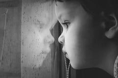 Portrait of a little kid looking in window. Royalty Free Stock Image