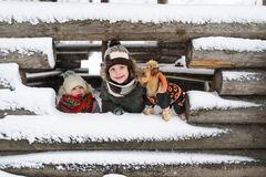 Portrait of the little kids and small dog against the background of the unfinished snow-covered house in the village.  royalty free stock photos
