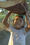 Portrait little Latino girl carrying firewood on head Royalty Free Stock Photo