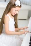 Portrait of little musician in white dress playing piano. Portrait of little girl in white dress playing piano. Concept of music study and creative hobby royalty free stock image